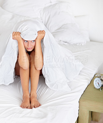 Buy stock photo Shot of a young woman sitting in her bed looking unhappy with having to wake up