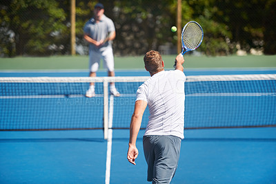 Buy stock photo Shot of two people playing tennis outside