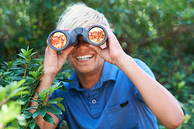 Buy stock photo A young boy looking through his binoculars