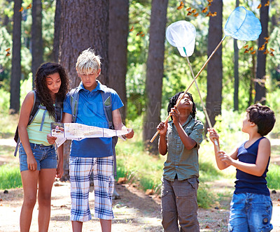 Buy stock photo Multi-ethnic kids exploring a map while standing outside in a forest