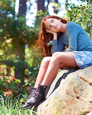 Buy stock photo A cute young red-haired girl sitting on a rock in a beautiful nature scene