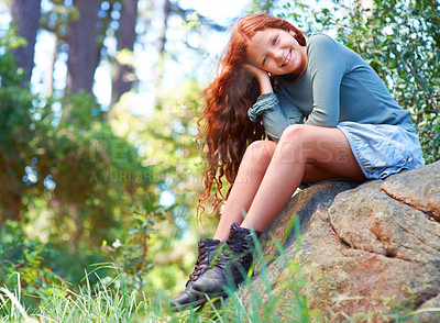Buy stock photo A young red-haired girl sitting on a boulder and smiling