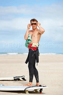 Buy stock photo Full length of a young surfer standing on the beach and putting on his shades