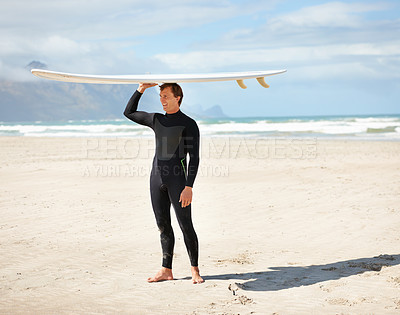 Buy stock photo Full length shot of a young surfer at the beach carrying his board on his head