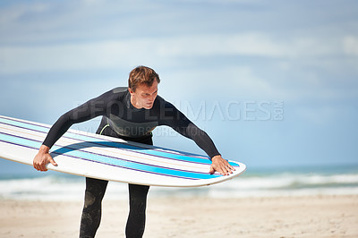 Buy stock photo A young man checking out his surfboard before hitting the waves