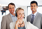 Smiling woman in headphones with office colleagues
