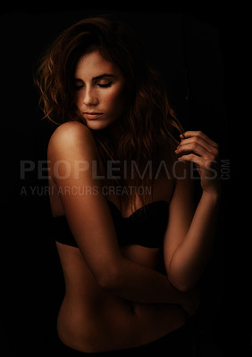 Buy stock photo A gorgeous young woman standing in a black bra against a dark background