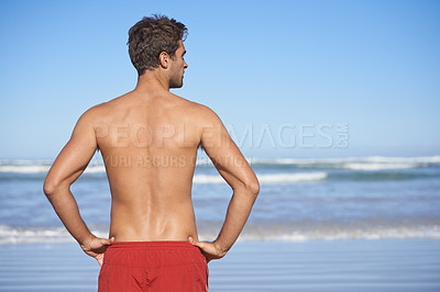 Buy stock photo Rear-view of a male lifeguard looking out at the ocean