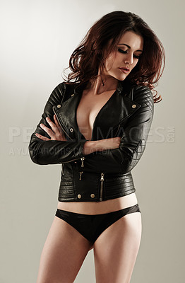 Buy stock photo An attractive young woman standing with her arms folded in a leather jacket and panties