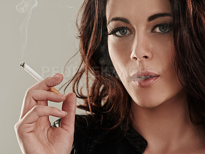 Buy stock photo Portrait of an attractive young woman smoking a cigarette