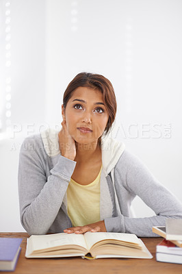 Buy stock photo Shot of a beautiful college student sitting at her desk and looking thoughtful