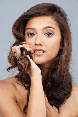 Buy stock photo Beautiful woman looking at the camera while holding her hair