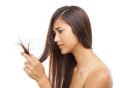 Buy stock photo A young woman looking at her split ends