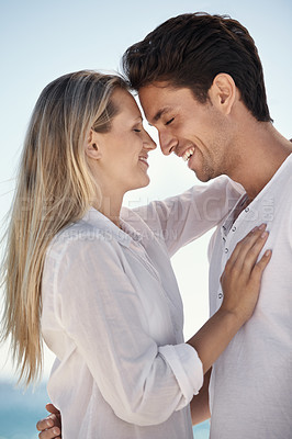Buy stock photo A happy young couple embracing on the beach