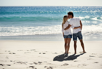 Buy stock photo A happy couple kissing on the beach with copyspace