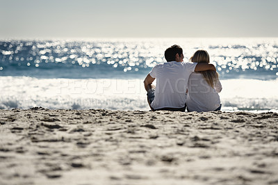 Buy stock photo A couple sitting on a beach -Back view