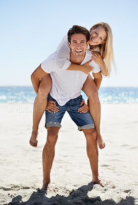 Buy stock photo A handsome young boyfriend giving his girlfriend a piggyback ride on the beach