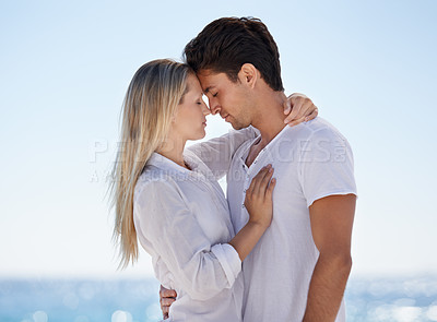 Buy stock photo A loving young couple embracing on the beach