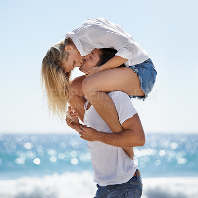 Buy stock photo A young couple piggybacking at the beach