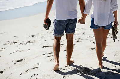 Buy stock photo Cropped image of a couple walking on the beach
