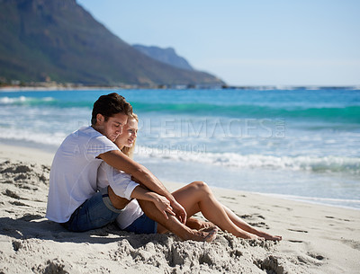 Buy stock photo A young couple sitting together on the beach and admiring the beautiful view