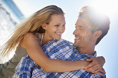 Buy stock photo A young, affectionate couple at the beach