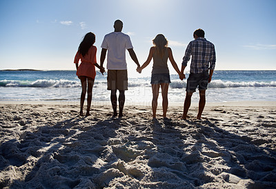 Buy stock photo Full length of two young couples looking away at the beach