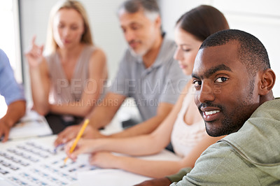 Buy stock photo An african american man glancing over his shoulder while involved in a project meeting
