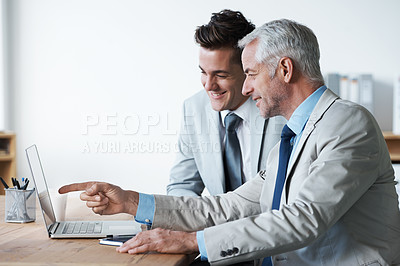 Buy stock photo Two corporate businessmen looking at a laptop