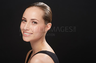Buy stock photo Cropped view of a naturally beautiful young brunette smiling against a black background