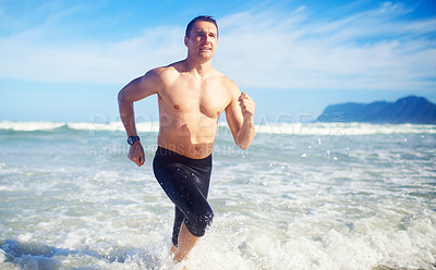 Buy stock photo A mature man running along the beach