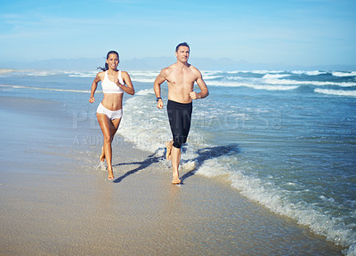 Buy stock photo Full length shot of two young people jogging along the beach