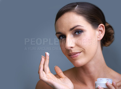 Buy stock photo Portrait of an attractive young woman applying moisturizer to her skin
