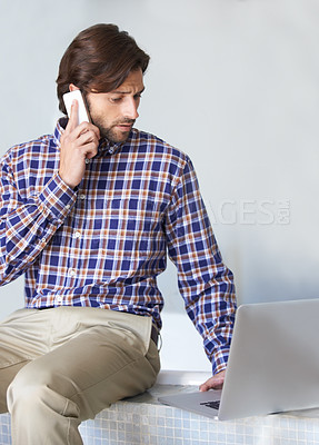 Buy stock photo A young man working on his laptop while talking on the phone
