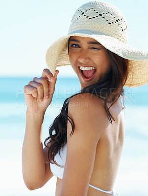 Buy stock photo A gorgeous young woman wearing a sunhat on the beach and winking at you