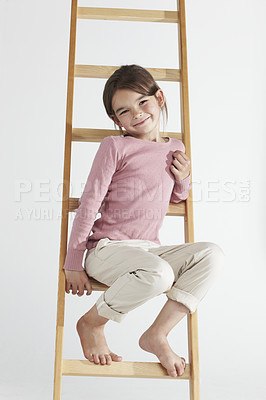 Buy stock photo Studio portrait of an cute little girl sitting on a ladder