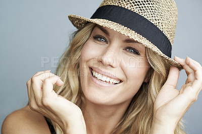 Buy stock photo Portrait of a gorgeous young blonde wearing a hat giving you a toothy smile