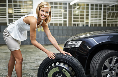 Buy stock photo A beautiful young woman changing her car's tyre in a parkade