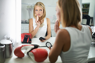 Buy stock photo A stylish young woman applying make-up with a pair of boxing gloves lying next to her