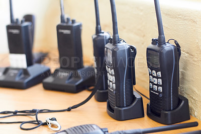 Buy stock photo Shot of a group of two-way radios in their chargers on a table