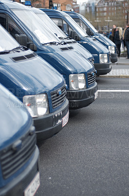 Buy stock photo Shot of a row of police patrol vehicles