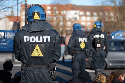 Buy stock photo Rearview shot of a police man in riot gear