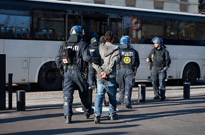 Buy stock photo Rearview shot of a police officer escorting an arrested protestor