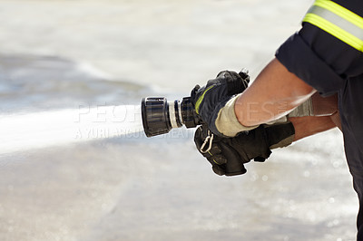 Buy stock photo Shot of a firemen holding a fire hose