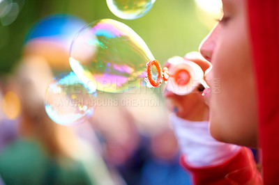Buy stock photo A young woman blowing bubbles outside - profile