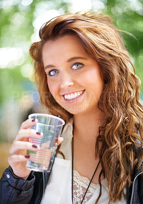 Buy stock photo A young woman standing outside holding a drink