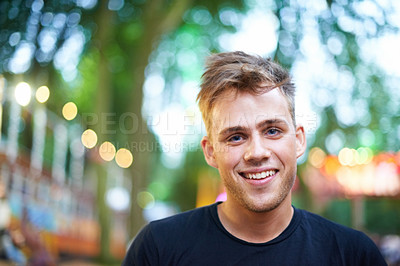Buy stock photo A handsome young man smiling at the camera while standing outside