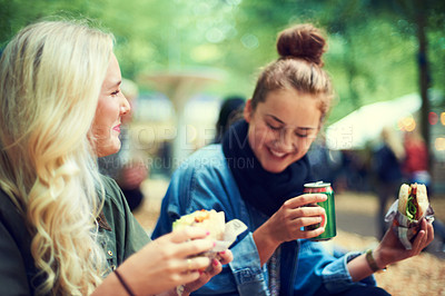 Buy stock photo Two young women drinking and having a snack at an outdoor festival