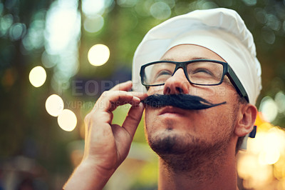 Buy stock photo A man adjusting his fake mustache while wearing glasses and a beret