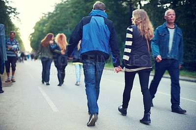 Buy stock photo Rear view of a group of people walking down a street